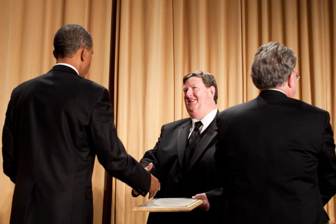 Michael Berens, The Seattle Times, receives congratulations from President Barack Obama for his 2011 Edgar A. Poe Award. (photo/Brendan Smialowski)